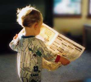 Boy reading newspaper | Online student success | Course retention rates