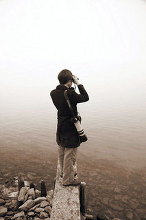Man looking over lake with binoculars | Find online school