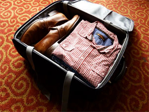 Study tips for traveling for online students - open luggage with clothes