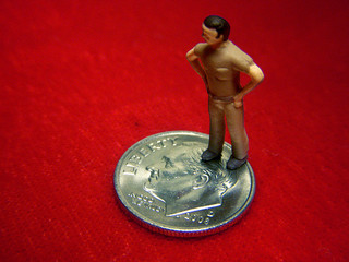 Online college course cost, figurine standing one a dime