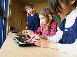 Technology in the classroom: students playing with an ipad