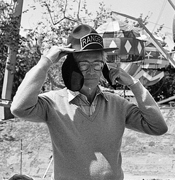 Black and white photo of Charles Schulz wearing a Snoopy hat