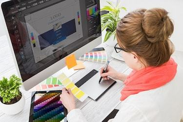 An online graphic design degree graduate at work
