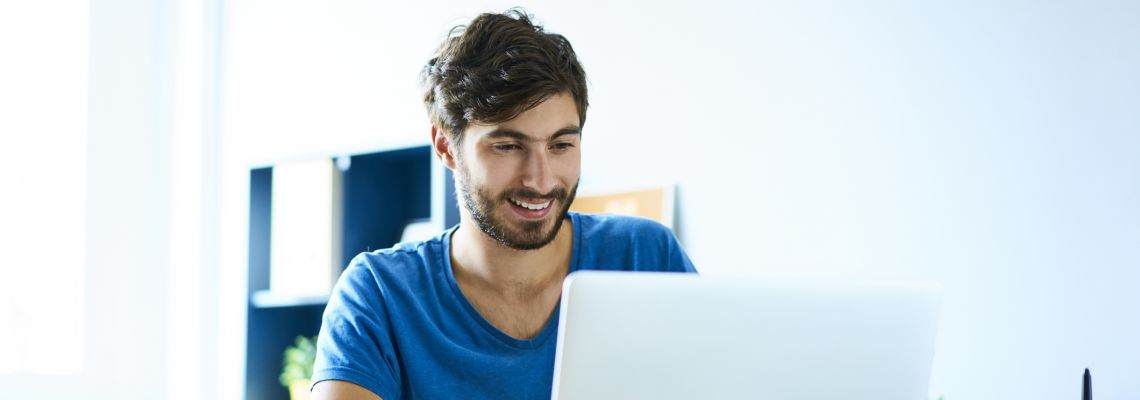 Smiling young man working on laptop in home office